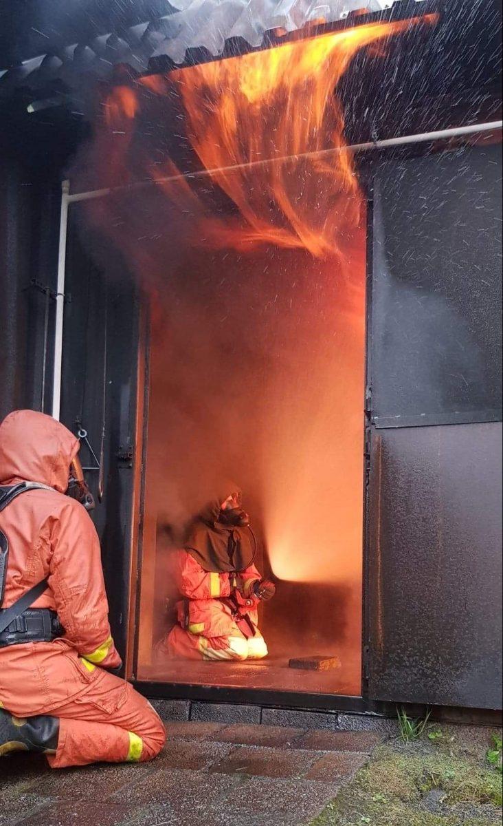 En brandman sitter i containern och övar på släckteknik